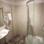 Umywalka, prysznic i grzejnik drabinkowy w pokoju hotelowym